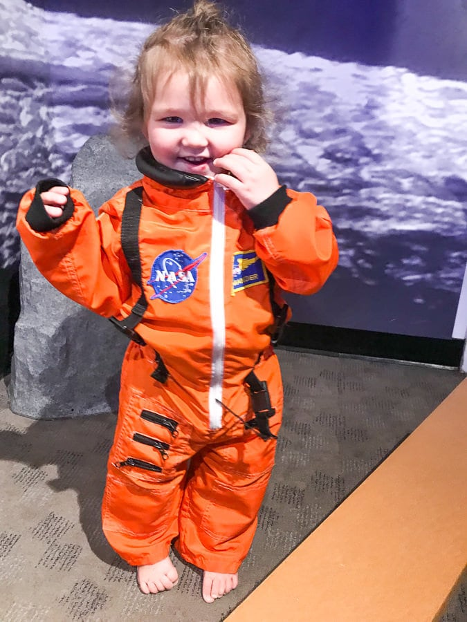 Little girl in nasa space suit visiting powerhouse science museum with her free museum tickets