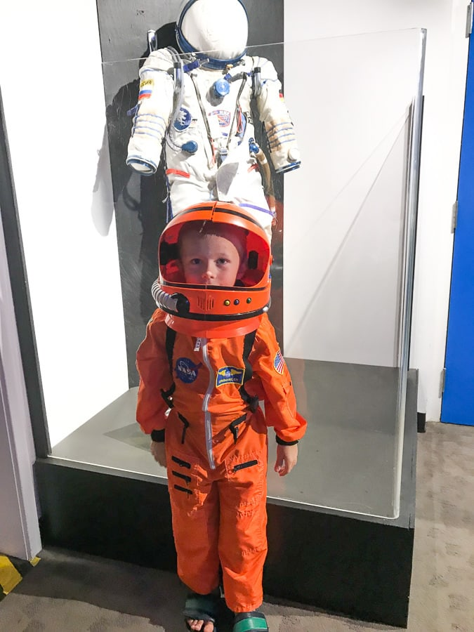 Little boy in orange space suit at powerhouse science center with free museum tickets.