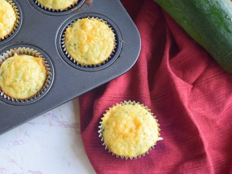 cheesy cornbread zucchini muffin on red cloth napkin next to muffin tin full of muffins and large zucchini