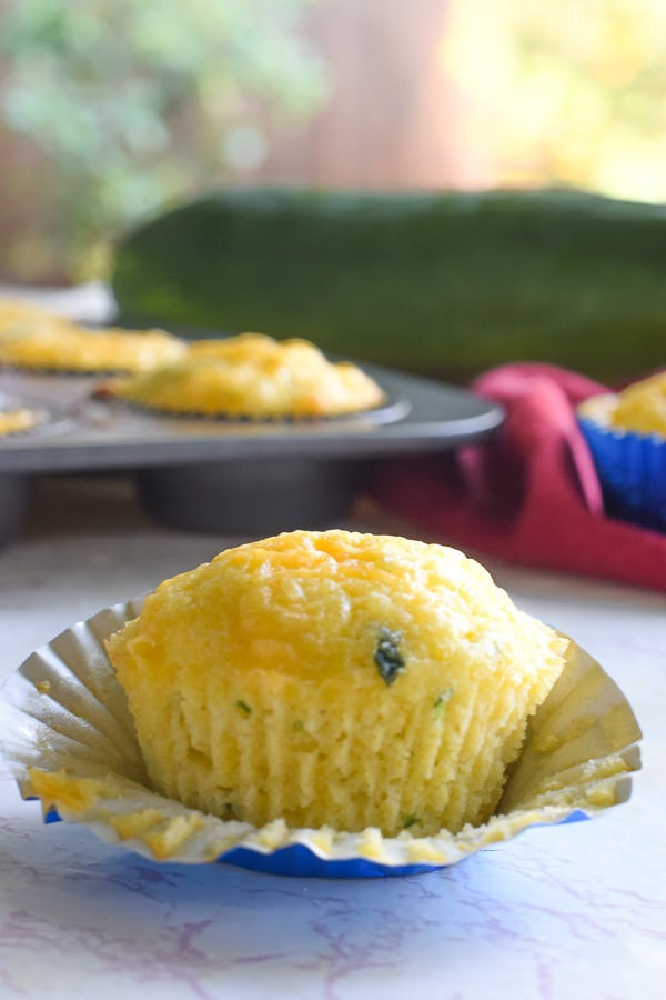 vertical shot of cheesy cornbread zucchini muffins on a white counter with a red cloth napkin