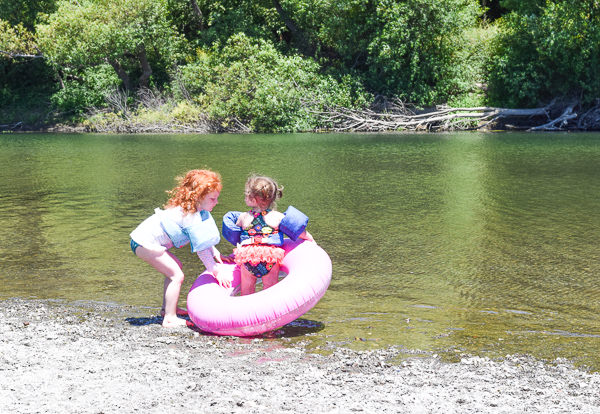 Two girls and a pink inner tube ready to swim in the Russian River.