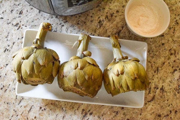 Steamed artichokes on a platter next to dipping sauce and an instant pot.