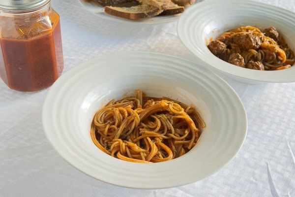 A bowl of cooked spaghetti topped in pressure cooker spaghetti sauce.