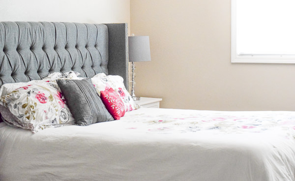 Bed with grey headboard, white floral bedding, two throw pillows.