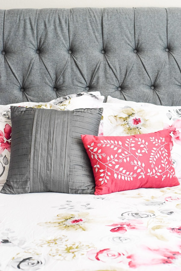 One grey and one red throw pillow on a bed with a grey headboard and white bedding