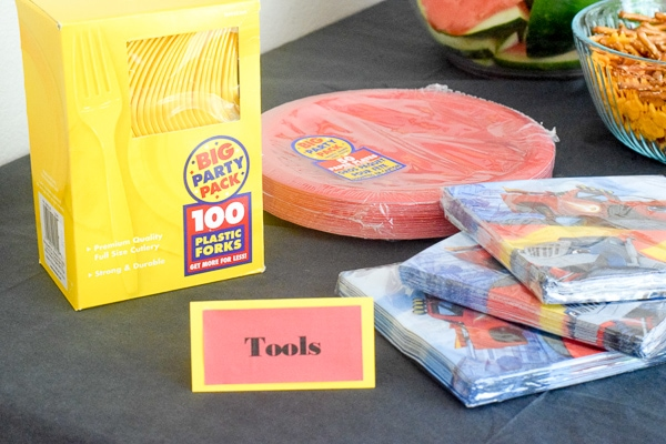 "Monster truck napkins, red plates, and yellow utensils with a sign that says ""tools"" for a monster truck party."