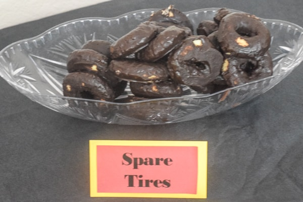 "Mini chocolate donuts with a sign that says ""spare tires"" for a monster truck themed birthday party."
