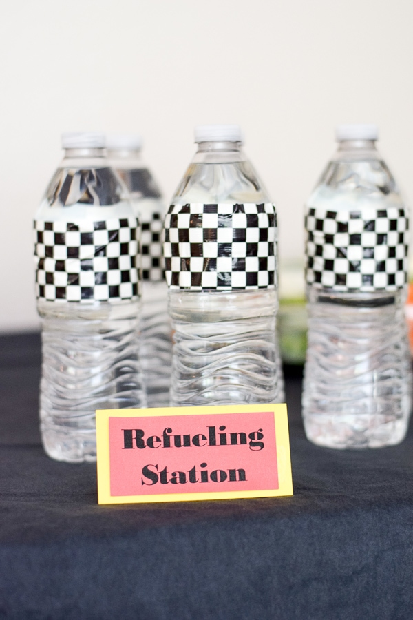 "Water bottles with black and white checkered labels and a sign that says ""refueling station""."