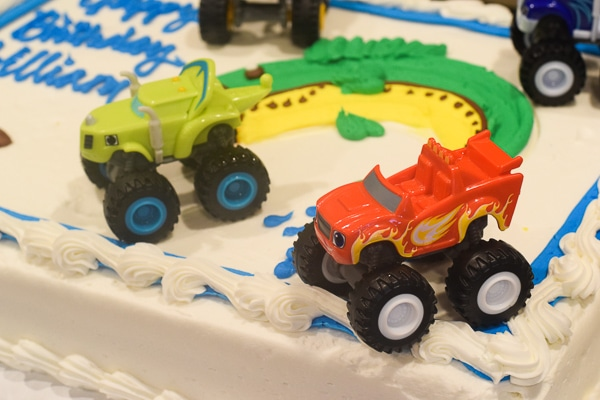 Blaze and the Monster machine toys on top of a costco sheet cake for an inexpensive monster truck themed party cake.