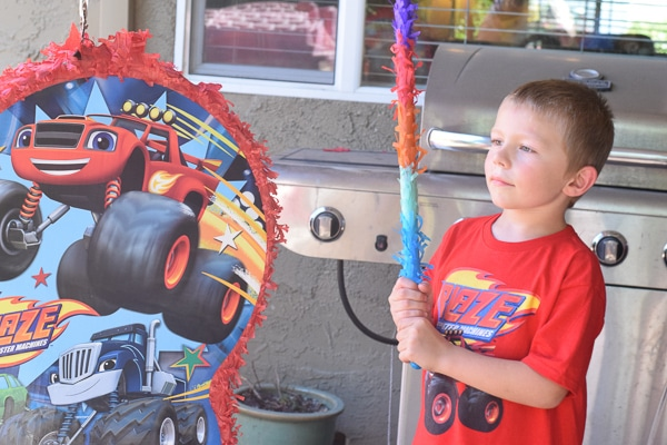 6 year old boy holding a pinata stick next to a monster truck pinata and wearing a monster truck shirt at his birthday party.