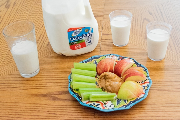 A gallon of Dairy Pure milk next to a plate of cut up celery, apples, and peanut butter