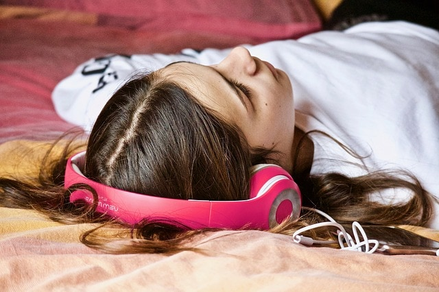 Women laying in bed with headphones on.