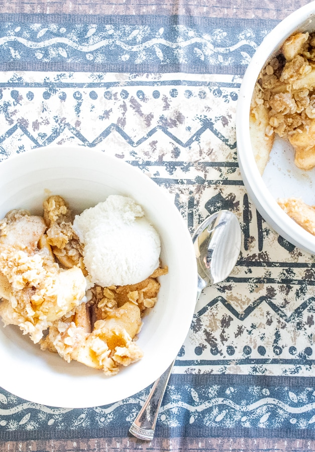 A bowl full of instant pot apple crisp and vanilla ice cream on top of a blue and brown patterned table cloth.