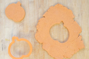 Pumpkin pie playdough rolled out on a cutting board and cut into a pumpkin shape.