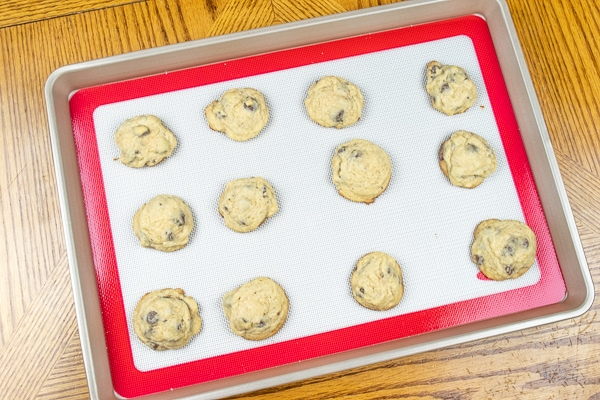 A dozen salted chocolate chip cookies fresh from the oven and still on the cookie sheet.