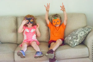 A boy and girl sitting on a couch and wearing Halloween masks.