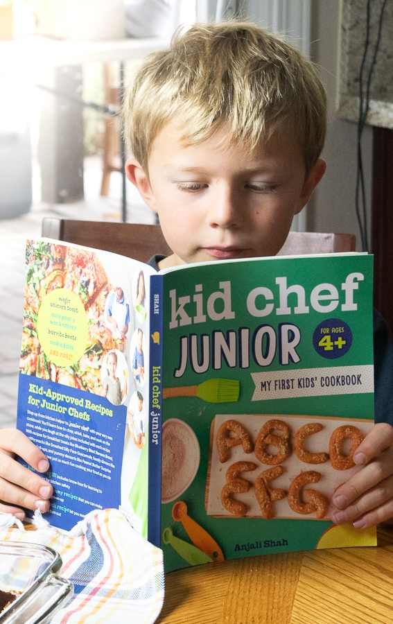 Boy reading the recipe for apple-cinnamon french toast bake in the kid chef junior cookbook.