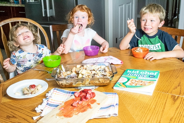 Three kids sitting around a table and taste-testing the apple-cinnamon french toast bake they made together.