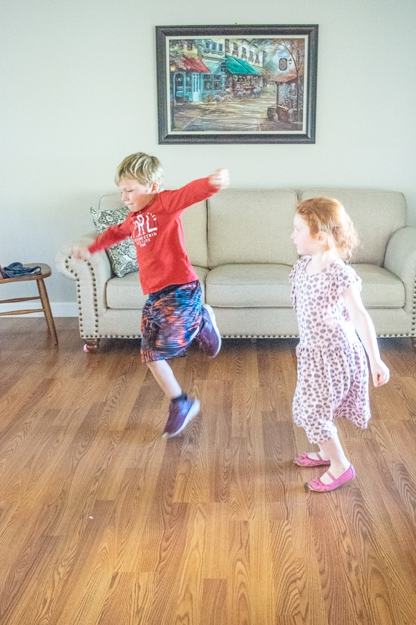 A brother and sister dancing together in a living room.