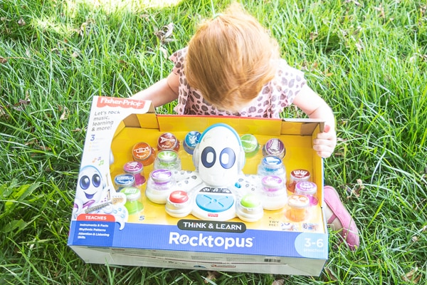 A little girl holding the best musical toy for preschoolers - a Think & Learn Rocktopus still in the box.