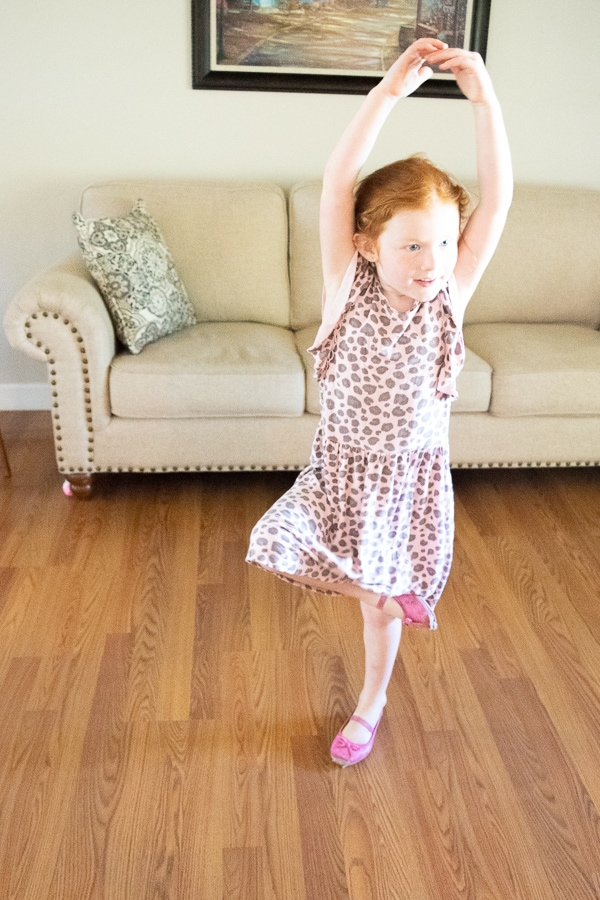 A little girl in a pink dress dancing in a living room.