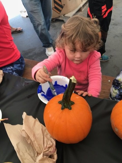 A toddler girl painting a pumpkin with blue paint during the Halloween festivities at Petaluma KOA.