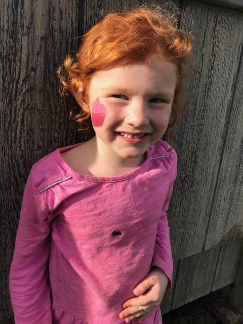 A red head 4 year old girl with a cupcake painted on her face.