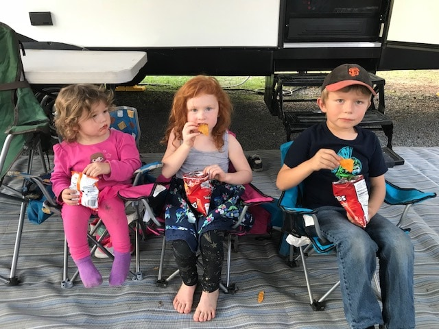 Three kids enjoying a snack at the Petaluma KOA.