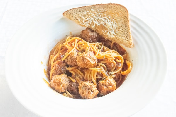 Pressure cooker spaghetti and meatballs in a white dish with a slice of garlic toast.
