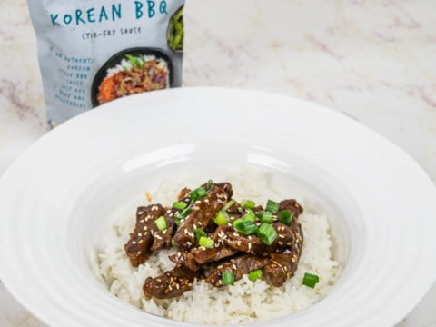Wide rimmed bowl of Korean BBQ Beef next to a package Passage to Asia Korean BBQ stir-fry sauce.