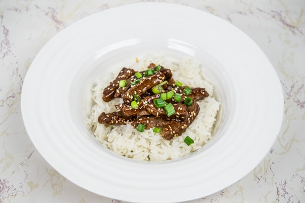 Korean BBQ Beef over jasmine rice in a white wide-rimmed bowl.