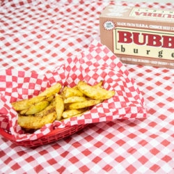A bowl of zesty fries next to a BUBBA burgers box.