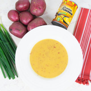 A bowl of creamy cheesy potato soup next to a can of Rico's Premium Cheddar, a batch of green onions, and red potatoes.