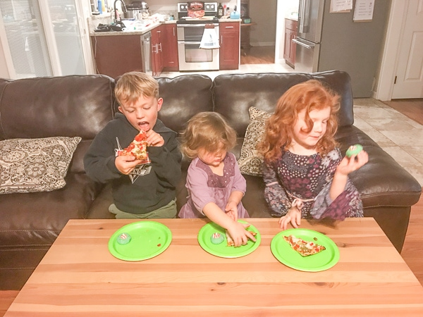 Kids sitting on a couch eating pizza and grinch cookies while watching How The Grinch Stole Christmas.