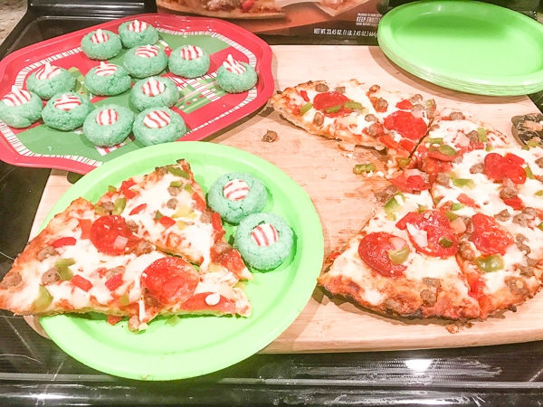 A plate of grinch christmas cookies next to a red baron supreme pizza.
