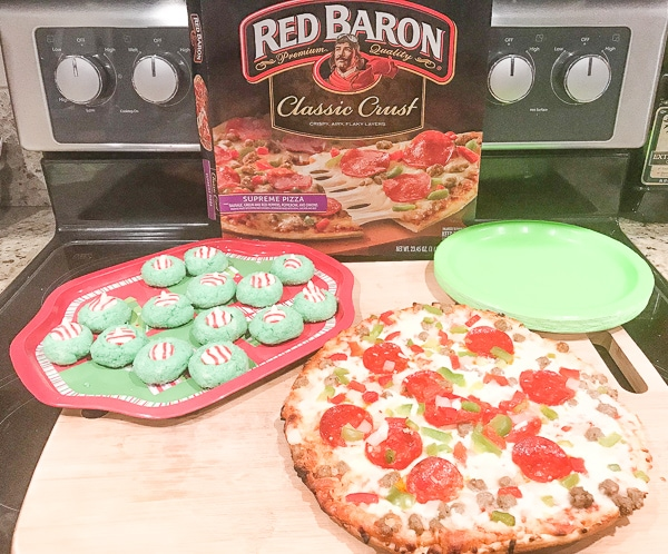 Dinner for a Grinch movie night: green plates, grinch cookies, and red baron pizza on a wooden cutting board.