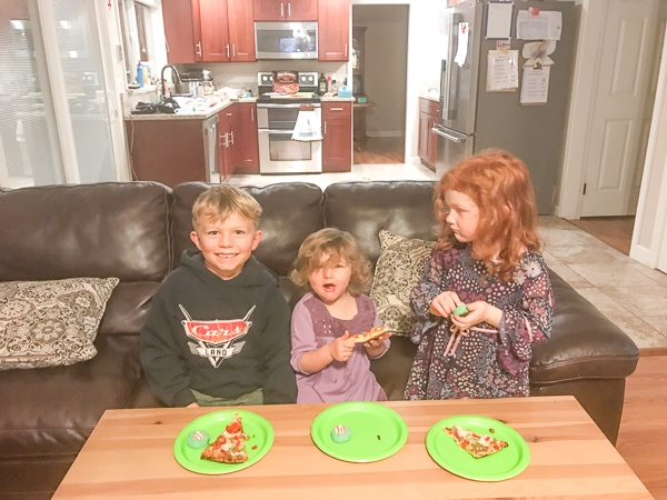 Three little kids sitting together on a couch ready for their dinner and movie night.