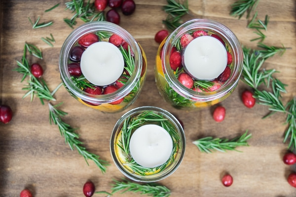 Holiday centerpieces made with fresh winter fruit in mason jars and topped with tealights.