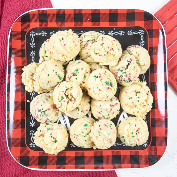 A buffalo plaid plate filled with a dozen christmas sprinkle pudding cookies.