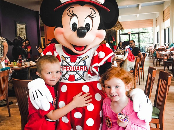 A boy and girl standing with Minnie Mouse at a Disneyland character breakfast.