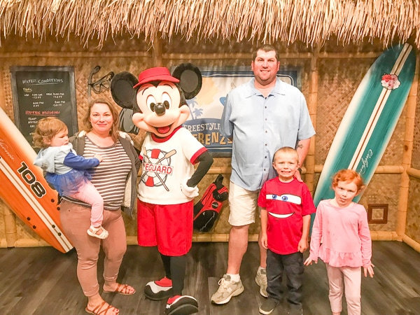 A woman and man with their three children, taking photo with Mickey Mouse at a character breakfast.