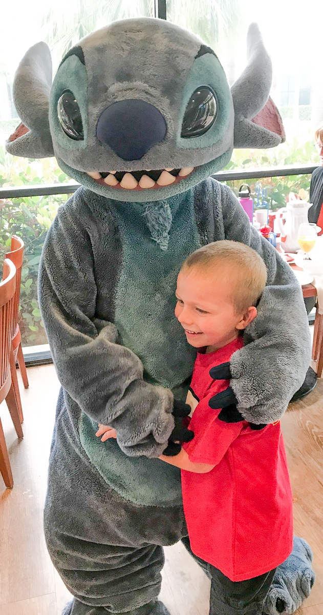 A boy hugging stitch during his Disneyland character breakfast.