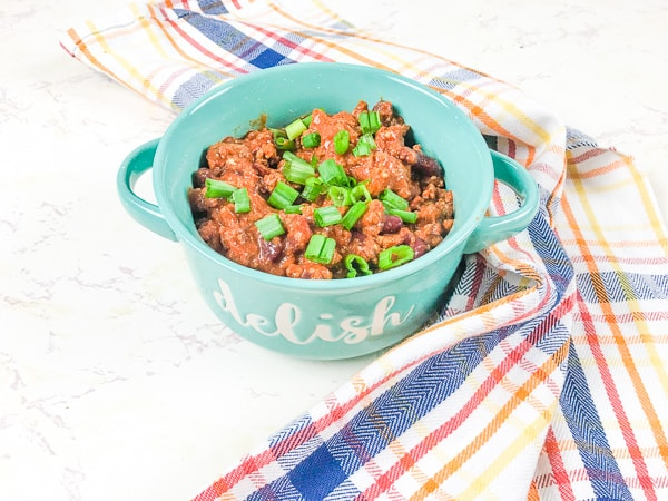 A bowl of instant pot beef chili topped with fresh green onions.
