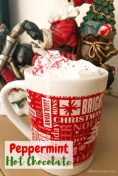 A cup of homemade peppermint hot chocoalte in front of a Santa figurine on a motorcycle.