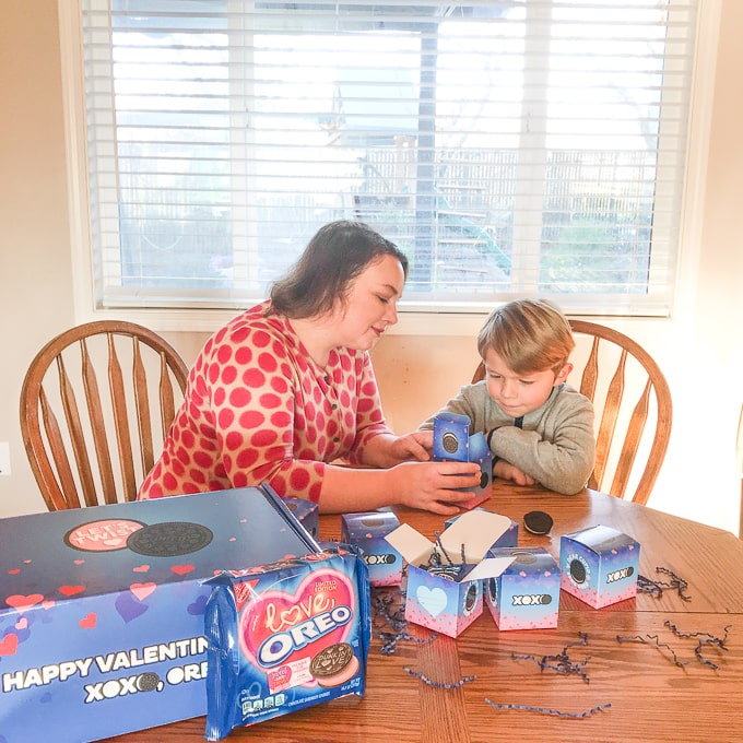 A boy and his mom putting together an OREO Valentine's Day Kit.