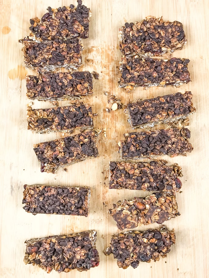 Chocolate chip granola bars cut up on a wooden cutting board.