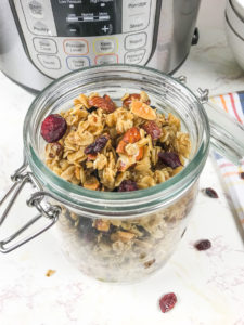 A close up of instant pot granola made with rolled oats, almonds, and dried cranberries