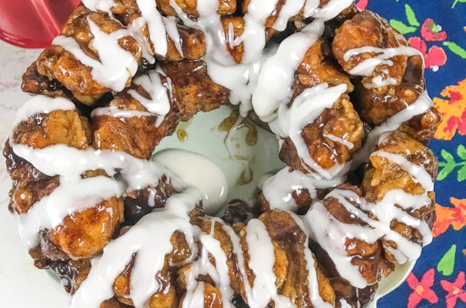 A fresh batch of instant pot monkey bread drizzled with icing and next to a floral hand towel.