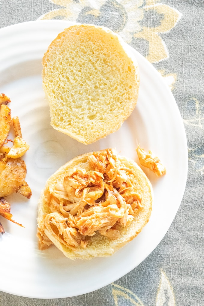 Instant pot pulled chicken on an opened hamburger bun.