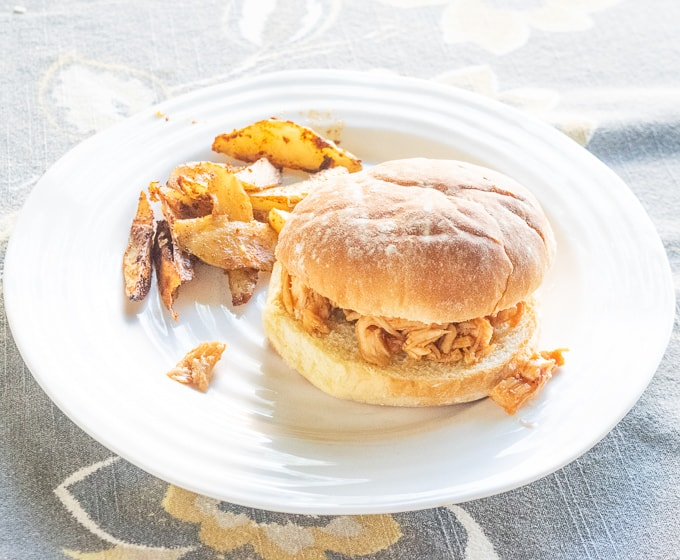 A pulled chicken sandwich on a white plate.